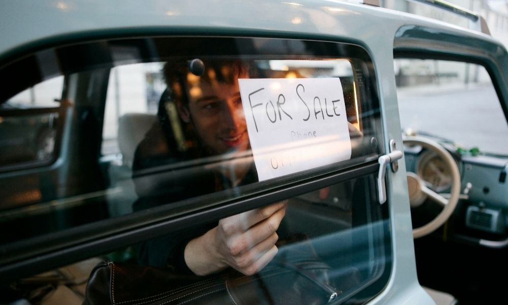man putting a for sale sign in his car to try and sell to local friends and neighbours.