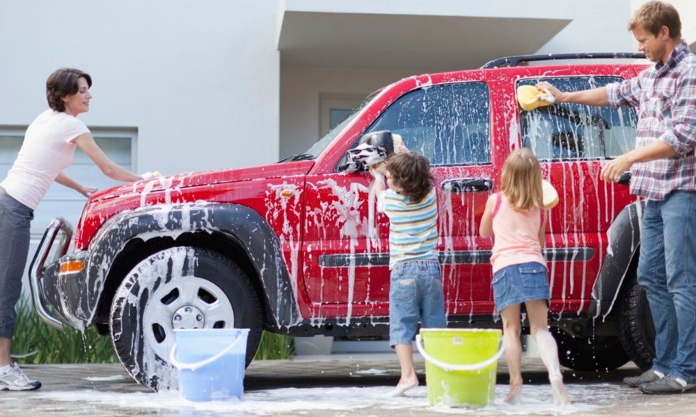 family showing kids how to wash a car