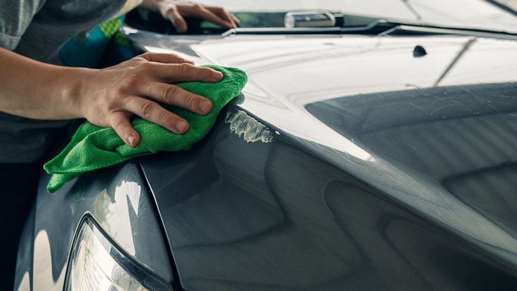 wiping down the surface of the car to fix the scratch